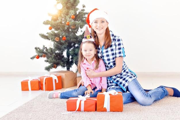Концепция рождества, семьи и праздников - праздничные мать и дочь дома в гостиной