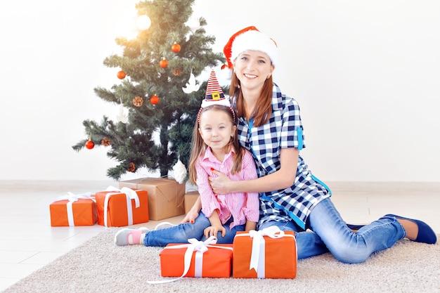 Концепция рождества, семьи и праздников - праздничная мать и дочь на диване у себя дома в гостиной