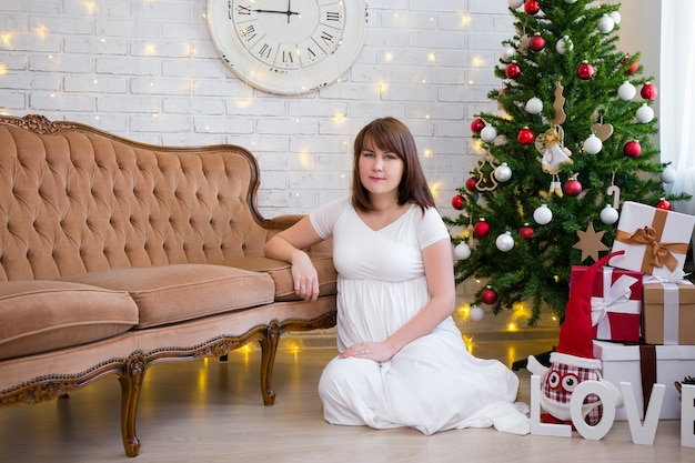 Christmas and family concept  beautiful pregnant woman at home with decorated christmas tree