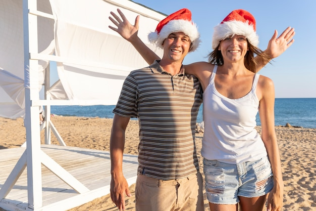 Christmas family couple husband and wife make selfie on the phone. man and woman wearing santa claus hats smiling, laughing celebrating new year on the sandy beach