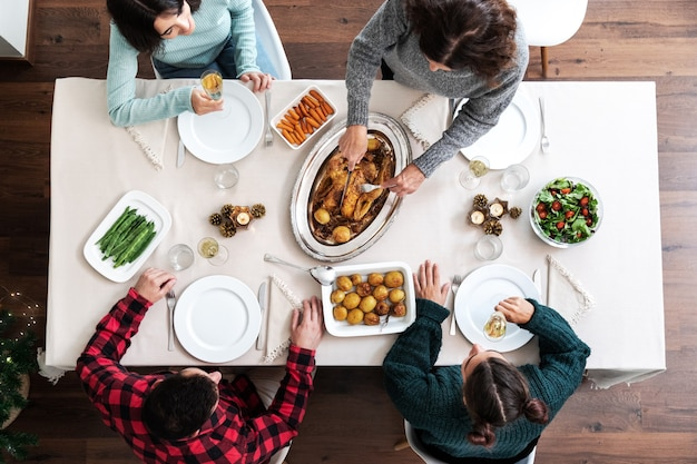 クリスマス家族ディナー上面図クリスマスローストチキンを彫る成熟した白人女性休日