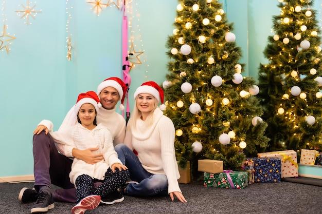 Рождество. семья. счастье. папа, мама и дочь в шляпах санты смотрят в камеру и улыбаются на полу дома