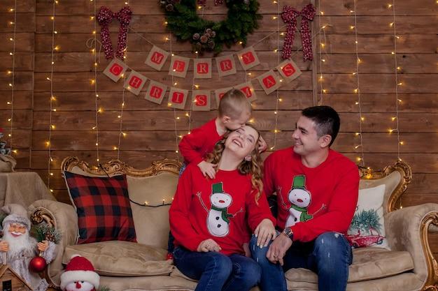 Рождественская семья. счастье. портрет папы, мамы и сына, сидящих на диване у себя дома возле елки, все улыбаются. концепция семейного зимнего отдыха.