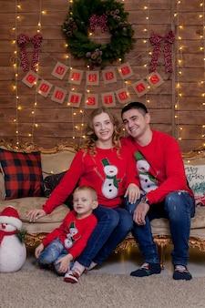 クリスマス家族の幸福お父さんのお母さんと自宅のソファに座っている息子の肖像画