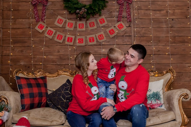 Рождество семейное счастье портрет папы, мамы и сыновей на диване у себя дома