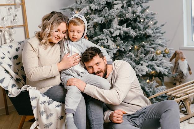 クリスマスツリーの近くで自宅で肘掛け椅子に座っているお父さん、妊娠中のママと幼い息子のクリスマス家族の幸福の肖像画抱擁笑顔ヨーロッパの若い大人の家族の休日の朝