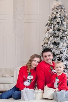 Рождество. семья. счастье. портрет папы, сына, сидящего на полу дома возле елки, все улыбаются.