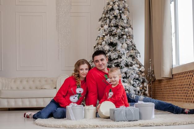 Рождество семейное счастье портрет папы и сына, сидящего на полу дома возле елки