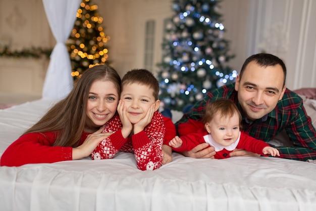 クリスマスの家族!幸せなママ、パパと小さな娘と息子、横になっています。休日の人々