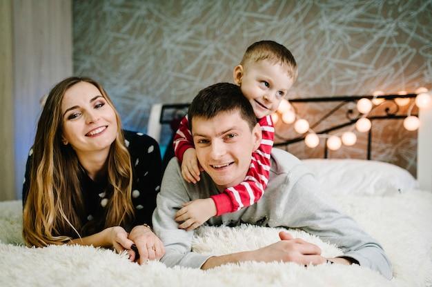 クリスマスの家族!幸せなママ、パパ、サンタクロースのセーターを着た幼い息子が横になっています。愛の抱擁、休日の人々を楽しんでいます。メリークリスマス、そしてハッピーニューイヤー。