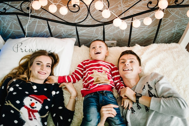 クリスマスの家族!幸せなママ、パパ、サンタクロースのセーターを着た幼い息子が横になっています。愛の抱擁、休日の人々を楽しんでいます。一体感の概念。フラットレイ。上面図。