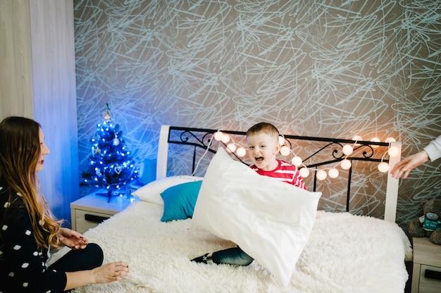 クリスマスの家族!幸せなママ、パパ、サンタクロースのセーターを着た幼い息子が枕で遊んでいます。愛の抱擁、休日の人々を楽しんでいます。メリークリスマス、そしてハッピーニューイヤー。