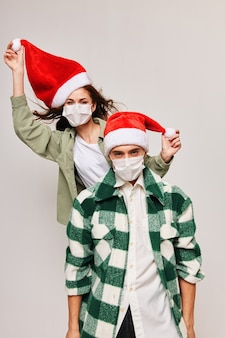 サンタの帽子と若い男のクリスマスの家族の休日の楽しい女性
