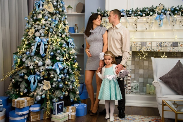 クリスマスの家族。ママとパパと一緒に家にいる小さな娘。