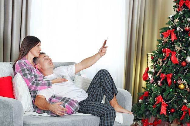 朝、ホームホリデーのリビングルームでクリスマス家族の肖像画