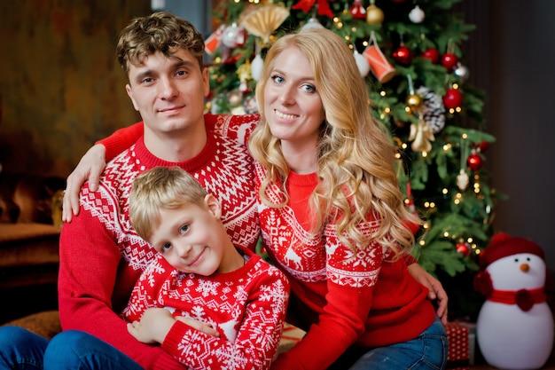 Рождественский семейный портрет в красных традиционных свитерах в домашней праздничной гостиной, родителях и ребенке с подарочной коробкой.