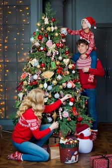 Christmas family portrait in red traditional sweaters in home holiday living room, parents and child with gift box.