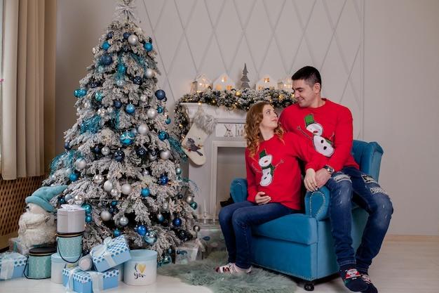 Рождественская семья улыбается возле новогодней елки