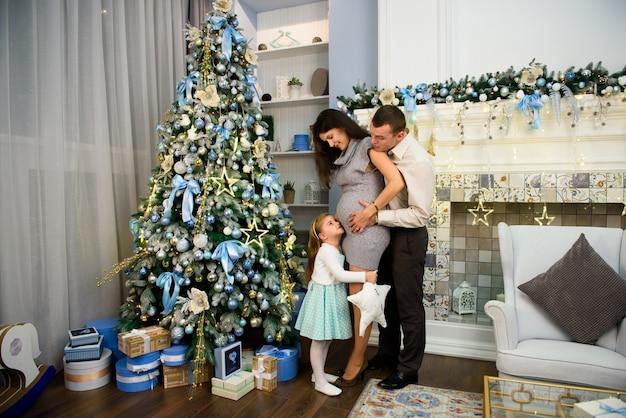 Рождественская семья стоит возле елки. гостиная украшена елкой и подарочной коробкой.