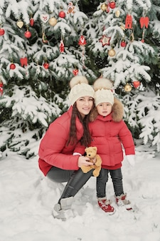 Christmas family in winter park. happy family mother and child daughter having fun, playing at winter walk outdoors. outdoor family fun on christmas vacation.winter clothing for baby and toddler.