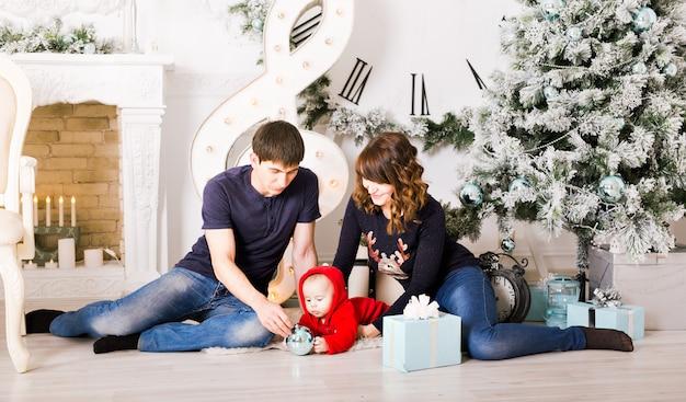 赤ちゃんオープニングギフトとクリスマスの家族。幸せな笑顔の親と子の自宅で新年を祝う