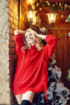 Christmas fashion sexy woman blonde in the red sweater, having fun and posing against the christmas tree and lamppost. winter and christmas tree in village house. girl with perfect figure and smile