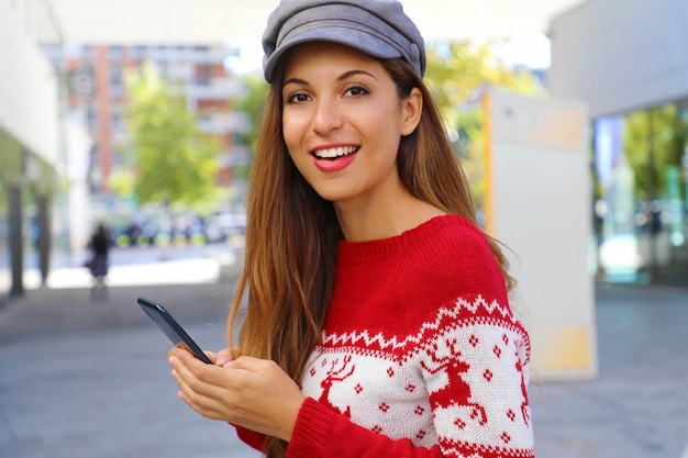 ショッピングファッションモールでスマートフォンでオンラインで購入するクリスマスファッション女性。