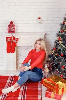 クリスマス気分。クリスマスパーティーの後。木製の壁のクリスマスツリーの近くで幸せそうな顔の女の子。