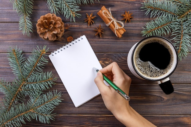 Christmas of female hands writing in opened notebook  on rustic wooden table covered with christmas decoration, top view, flat lay