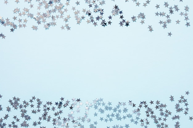 Christmas festive abstract backround with silver foil confetti stars on blue