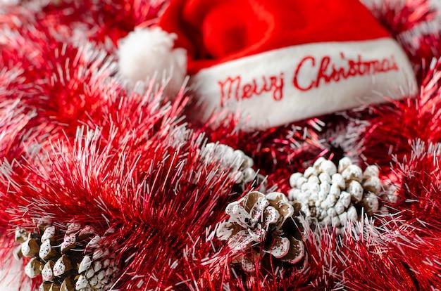 クリスマスのお祭りの背景。コーン、赤い花輪、サンタ帽子