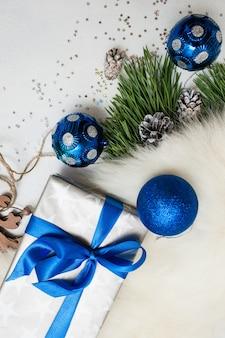プレゼントのクリスマスのお祭りの背景。銀の紙のギフトボックスに包まれ、毛皮と松で青いボールと横分体を飾り、コピースペースのある上面図。おめでとうと手作りの装飾コンセプト