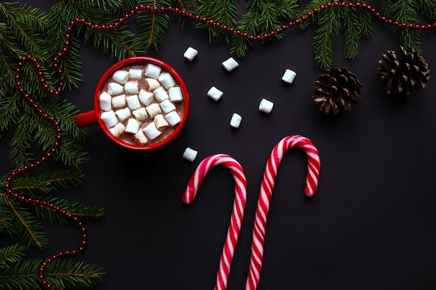 Christmas festive background with christmas tree branches, pine cones, hot chocolate and candy canes