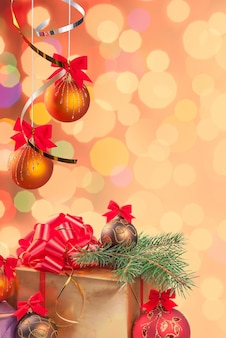 Christmas festive background with gifts, balls on ribbon and green branch