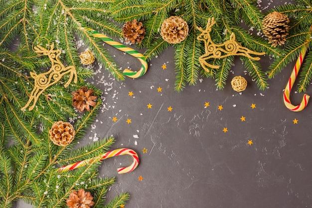 가문비나무 가지, 황금 사슴, 원뿔, 전통적인 장식 - 카라멜 - 지팡이, 별에서 온 색종이 조각이 있는 크리스마스 축제 배경.