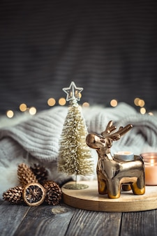 Christmas festive background with toy deer, blurred background with golden lights and candles