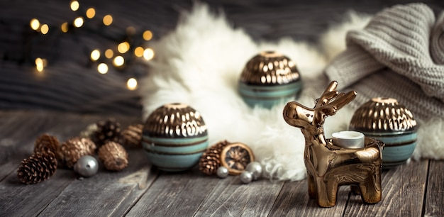Sfondo festivo di natale con cervi giocattolo con una confezione regalo, sfondo sfocato con luci dorate, sfondo festivo sul tavolo di ponte di legno