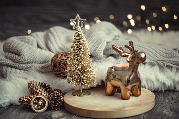 Christmas festive background with toy deer with a gift box, blurred background with golden lights