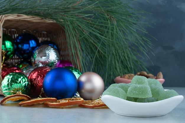 Рождественские праздничные шары с белой тарелкой, полной зеленого мармелада. фото высокого качества