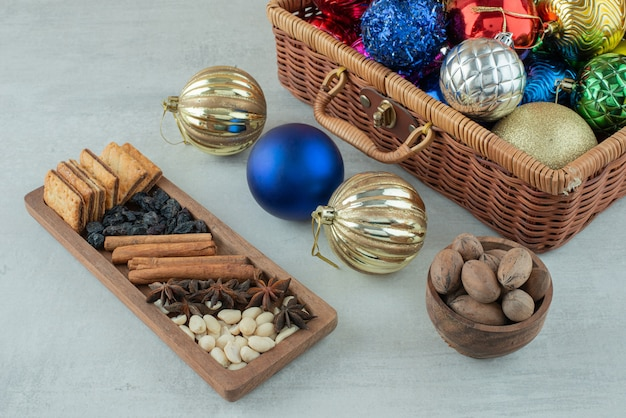 Christmas festive balls with wooden plate of cinnamon sticks, star anise on white background. high quality photo
