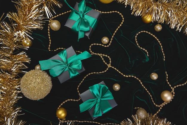 ベロアに緑のリボンが付いたクリスマスのお祝いの黒いギフトボックス