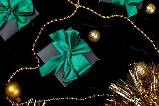 Christmas festive black gift boxes with green ribbon on velours glitte