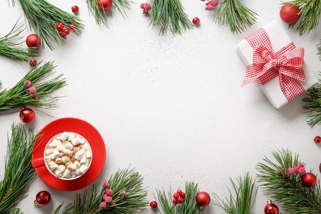 Рождественские праздничные границы кофе с зефиром и подарком на белом фоне. рождественская праздничная открытка с копией пространства. вид сверху, плоская планировка.