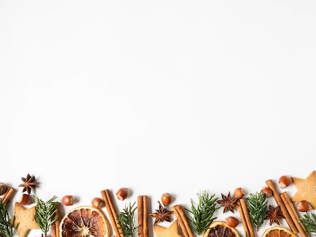 Christmas festive border with dry orange slices, cookies, fir tree, nuts and spices on white background