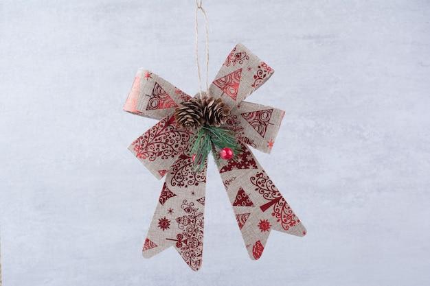 白い背景の上の松ぼっくりとクリスマスのお祝いの弓。