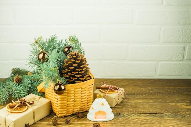 나무 테이블에 크리스마스 축제 구성입니다. 큰 삼나무 콘, 가문비나무 가지, 선물, 뜨거운 촛불이 있는 고리버들 바구니.