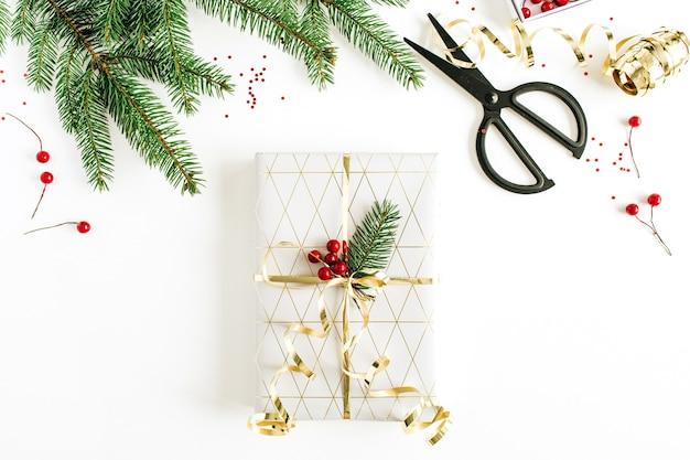 装飾されたギフトボックス、モミの枝、白い表面に赤いベリーとクリスマスのお祝いの構成。フラットレイ、上面図