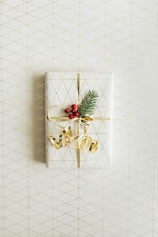 ギフトボックス、モミの枝、赤いベリー、金色の装飾が施されたクリスマスのお祝いの構成。上面図