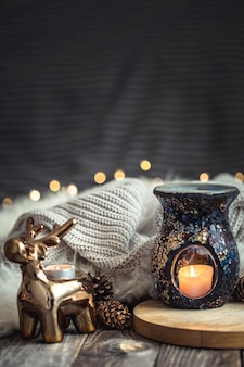 Новогодняя праздничная композиция с игрушечным оленем, золотыми огоньками и свечами на деревянном столе и зимнем свитере