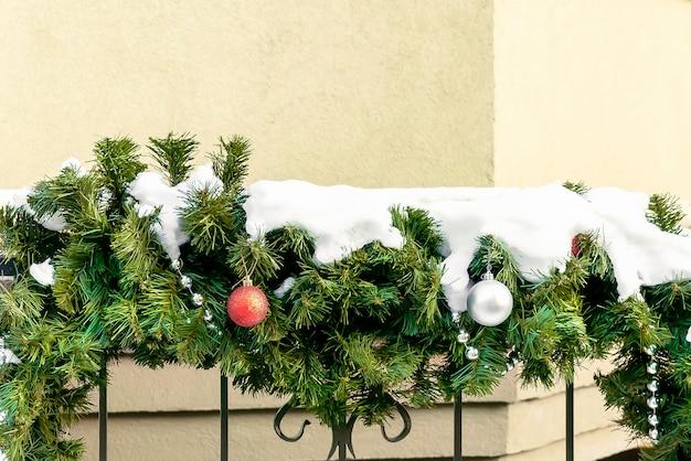 거리 크리스마스 새해 데코에 눈이 있는 전나무 가지에 공이 매달려 있는 크리스마스 축제 장식